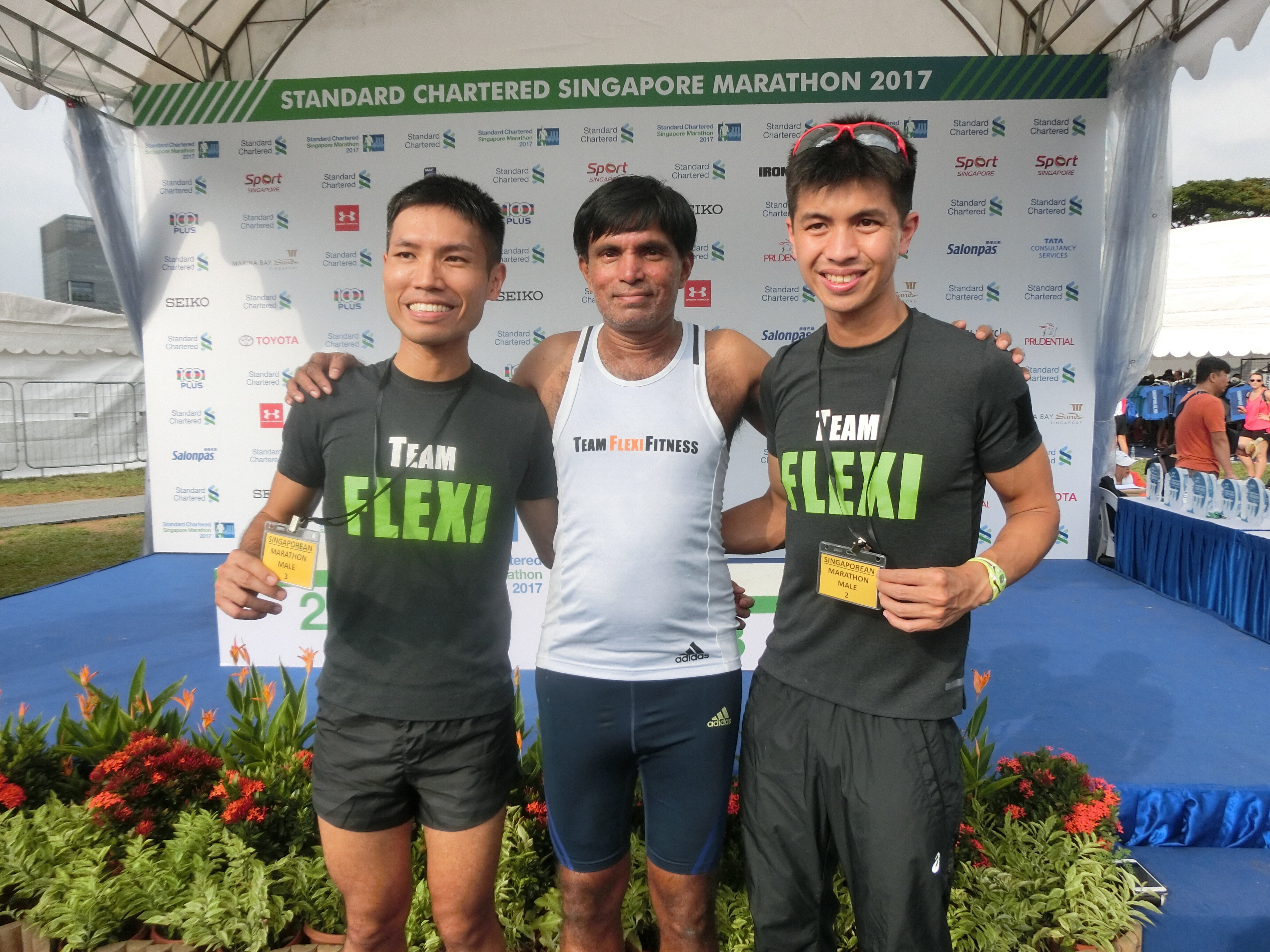 1st runner-up Ashley Liew (right) and 2nd runner-up Evan Chee (left) together with their Team Flexifitness coach and reigning Singapore marathon national record holder M. Rameshon (centre)